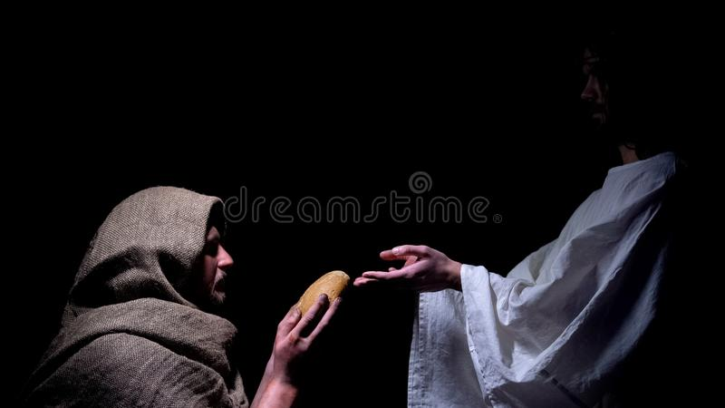 Mercy Jesus in crown of thorns giving bread for hungry homeless man, miracle. Stock photo stock image