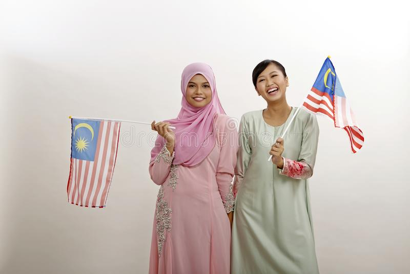 Merdeka. Two malay women holding malaysia flag stock photo