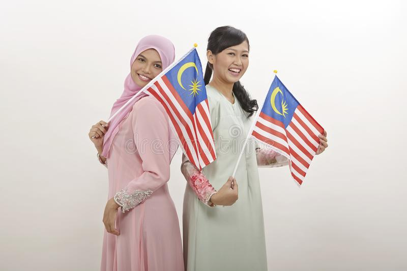 Merdeka. Two malay women holding malaysia flag royalty free stock images