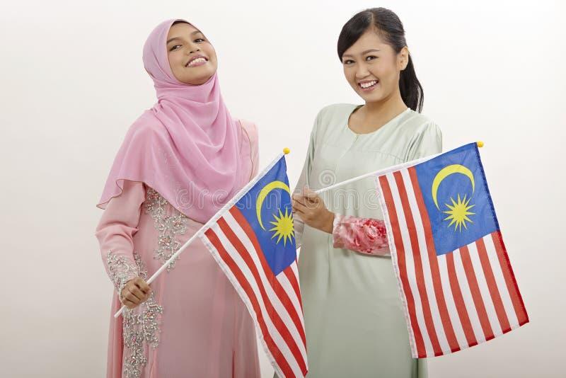Merdeka. Two malay women holding malaysia flag stock photography
