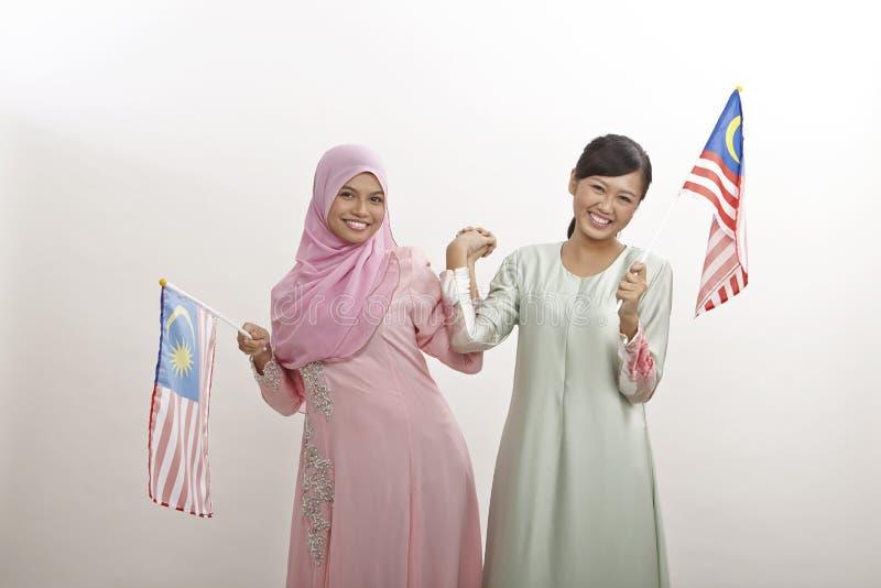 Merdeka. Two malay women holding malaysia flag stock photos