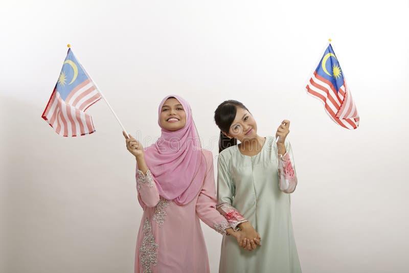 Merdeka. Two malay women holding malaysia flag royalty free stock photo