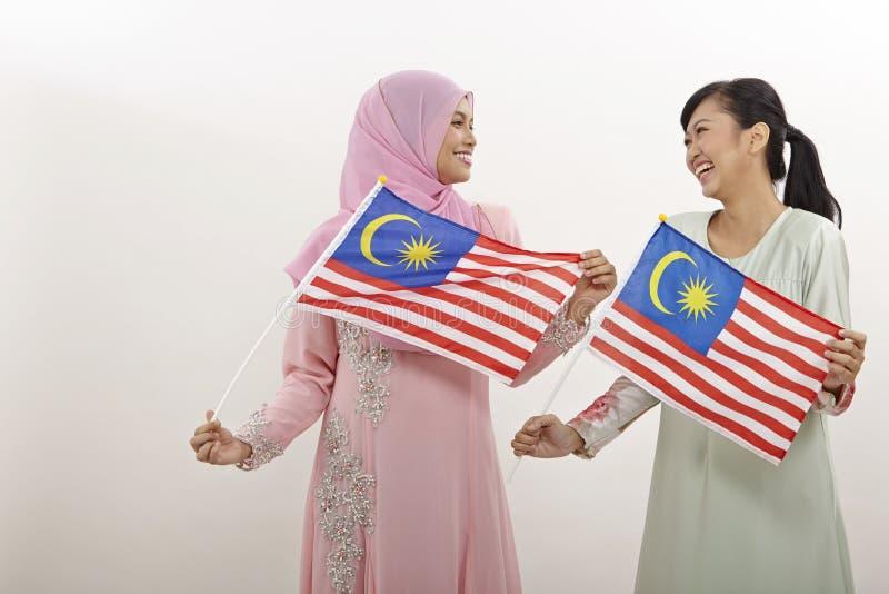 Merdeka. Two malay women holding malaysia flag royalty free stock photography