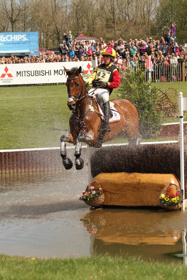 Merel Blom jumping at the Lake. Merel Blom from the Netherlands and his horse Rumour Has It jump the skinny brush fence in the water at the Lake during the cross royalty free stock images