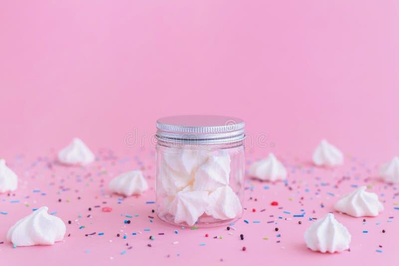 Merengues blancos en el tarro de cristal en fondo rosado imágenes de archivo libres de regalías