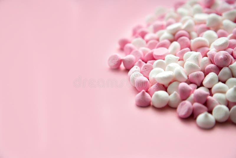Merengues do rosa e as brancas mini na forma das gotas, que se encontram em um fundo cor-de-rosa Lugar para o texto fotografia de stock royalty free