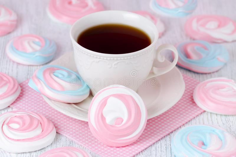 Merengues en colores en colores pastel con una taza de café y de una servilleta rosada foto de archivo libre de regalías