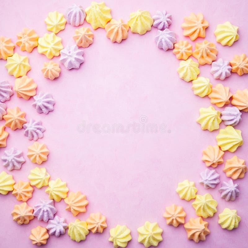 Merengues en el fondo rosado en colores pastel, plantilla de la comida fotografía de archivo libre de regalías