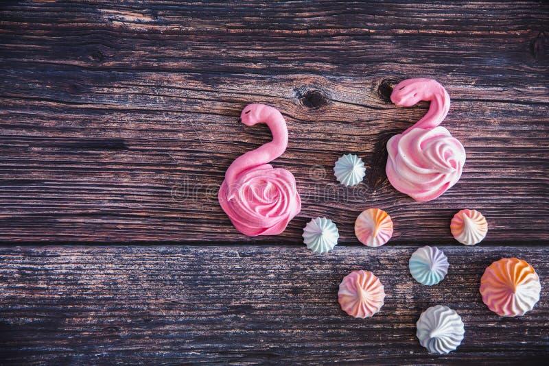 Merengues hechos en casa dulces coloridos bajo la forma de flamenco en fondo de madera Muchos c?firos dulces Visi?n superior de m fotografía de archivo