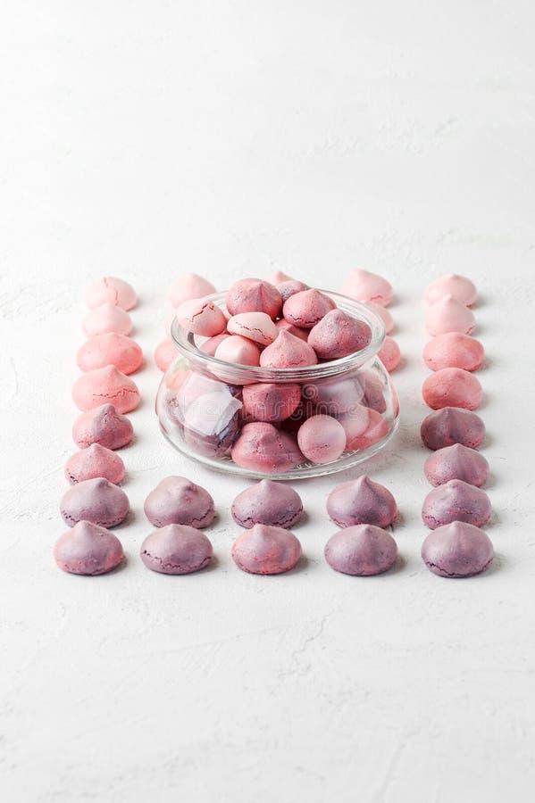 Merengues multicolores en colores violeta-rosados en un tarro de cristal y fotografía de archivo libre de regalías