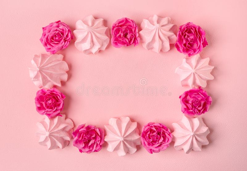 Merengues rosados en un fondo rosado con las rosas fotografía de archivo
