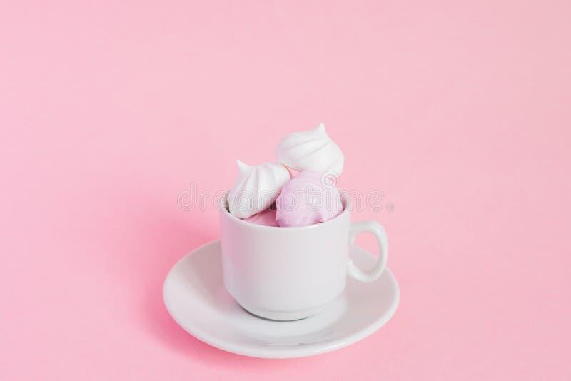 Merengues torcidas brancas e cor-de-rosa em um copo pequeno do coffe da porcelana no fundo cor-de-rosa Sobremesa francesa prepara fotos de stock royalty free