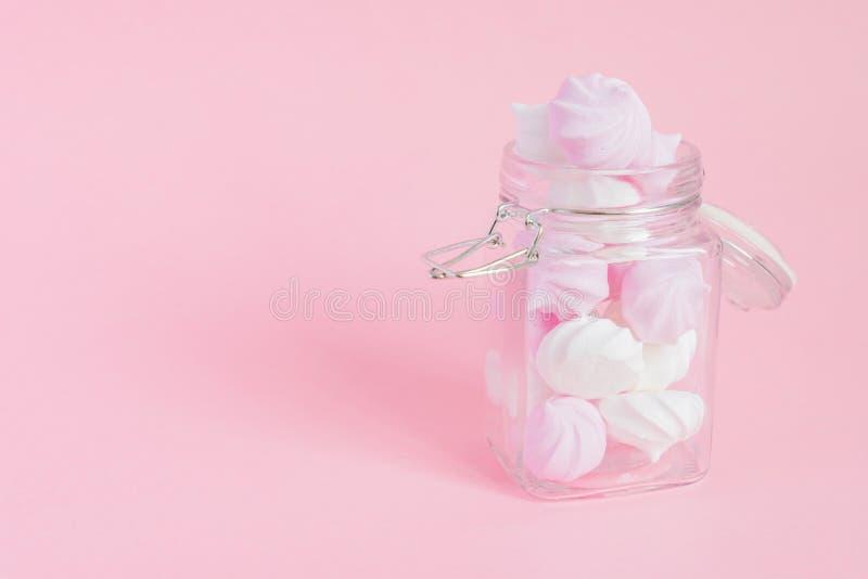 Merengues torcidas brancas e cor-de-rosa em um frasco de vidro no fundo cor-de-rosa Sobremesa francesa preparada do chicoteado co fotos de stock