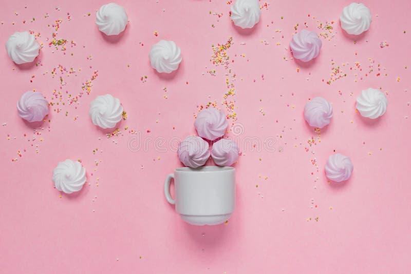 Merengues torcidos blancos y rosados en cuenco de la porcelana y peakles coloridos skattered en el fondo rosado, tarjeta de felic imagen de archivo