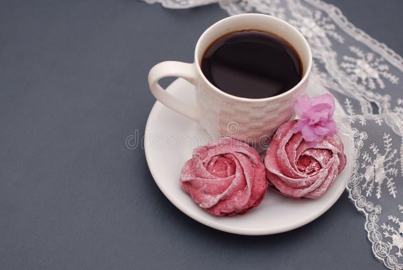 Merengues y taza de café rosados dulces en fondo del gris azul con las flores y el cordón de la orquídea Fondo de la primavera co foto de archivo libre de regalías