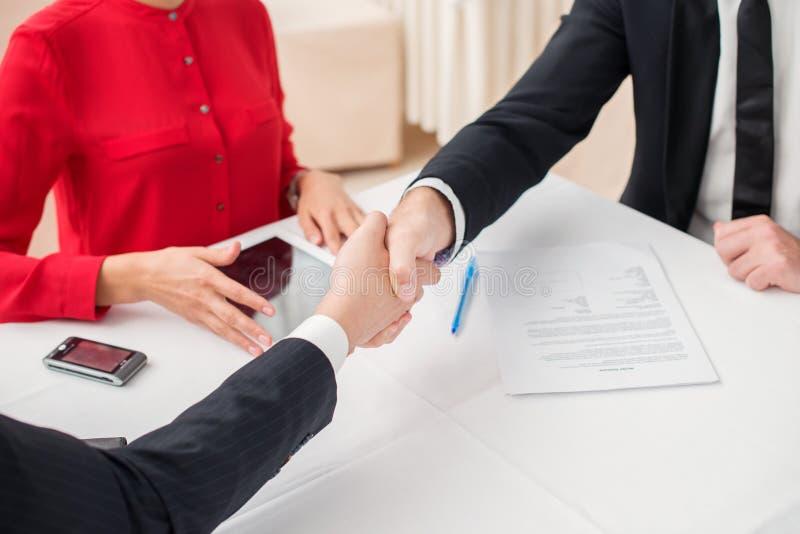 merger Lyckade tre och säker businesspeopleskakahand fotografering för bildbyråer