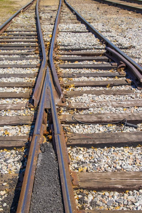 The merging of the tracks - two old rusty rail lines come together with a few fall leaves scattered among the gravel - selective stock photos