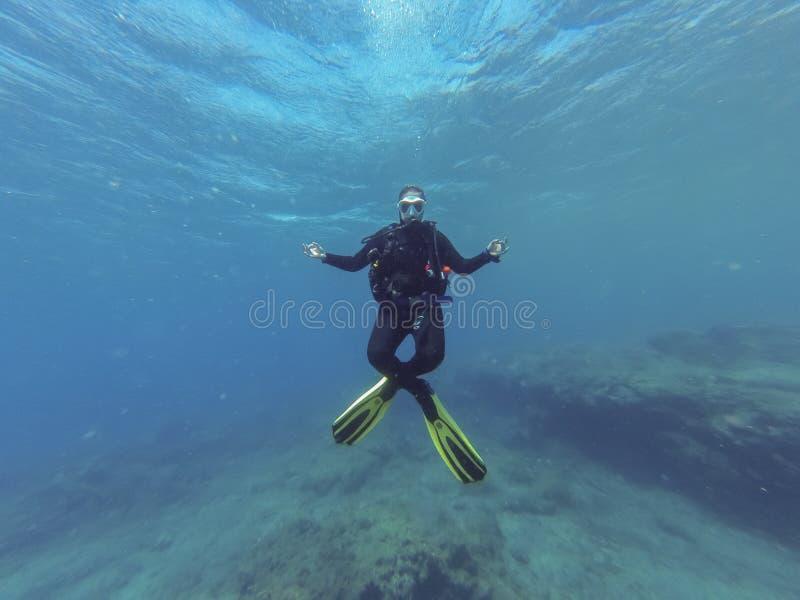 Mergulhador de mergulhador fêmea novo na posição da ioga dos lótus durante um mergulho em Oceano Atlântico fotografia de stock