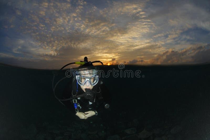 Mergulhador do mergulhador na água antes de um mergulho do nascer do sol fotos de stock