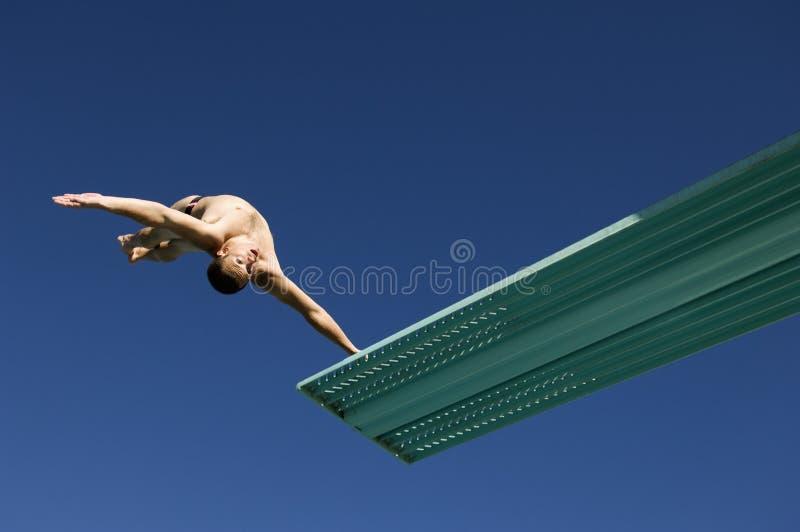 Mergulhador masculino que mergulha para trás em Mid Air imagem de stock royalty free