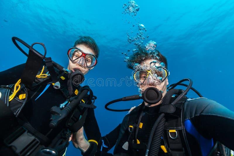 Mergulhadores de mergulhador da jovem mulher e do homem que fazem o selfie fotografia de stock
