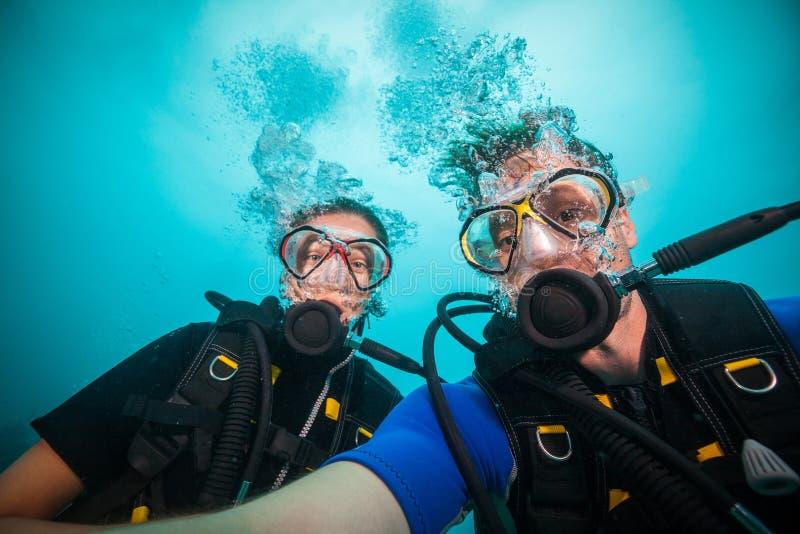 Mergulhadores de mergulhador da jovem mulher e do homem que fazem o selfie imagens de stock
