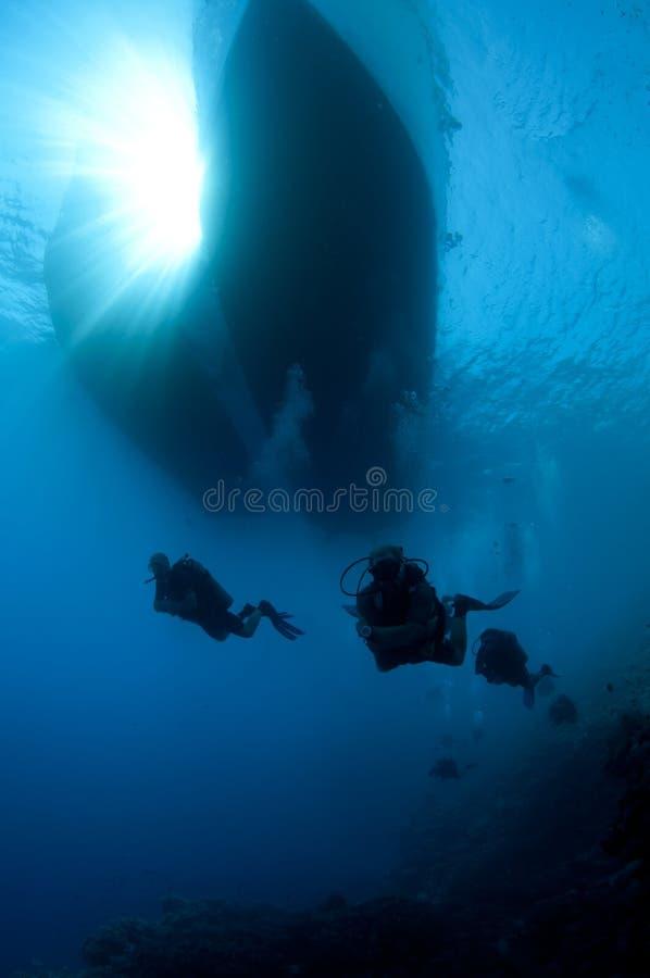 Mergulhadores do mergulhador sob um barco no oceano fotos de stock royalty free