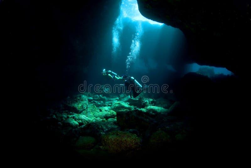 Mergulhadores que exploram uma câmara de ar de lava fotografia de stock royalty free