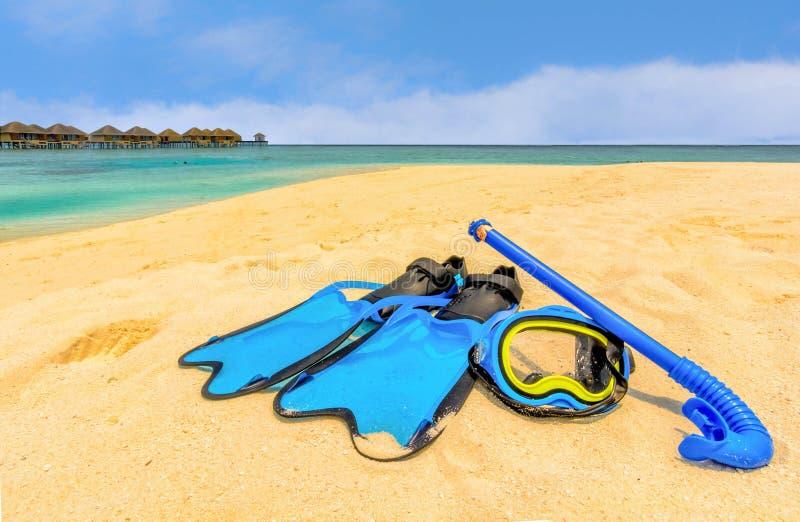 Mergulhando a engrenagem na praia com bungalows da água e na praia mim foto de stock royalty free