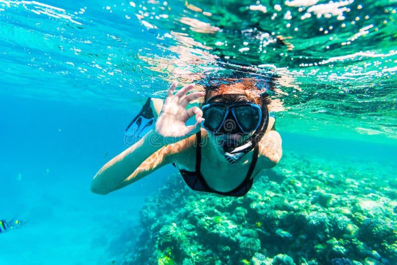 Mergulhar subaquático da mulher com natação aprovada do sinal no mar fotos de stock