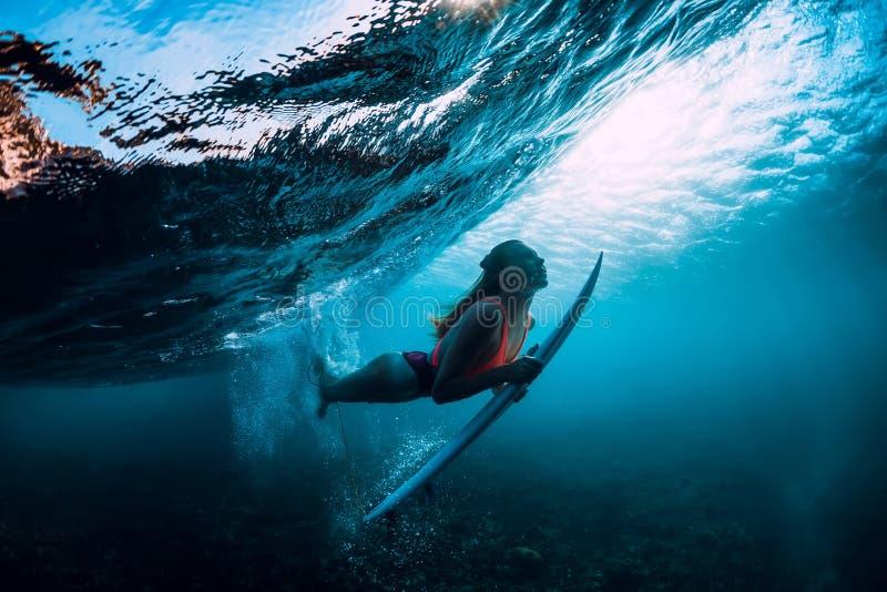 Mergulho atrativo da mulher do surfista subaquático com luz abaixo da onda e do sol fotos de stock royalty free