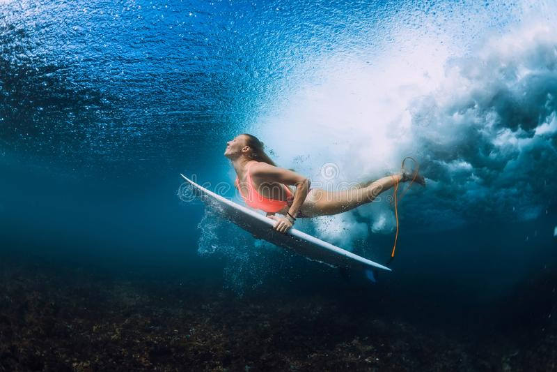 Mergulho atrativo da mulher do surfista subaquático com onda inferior imagens de stock royalty free