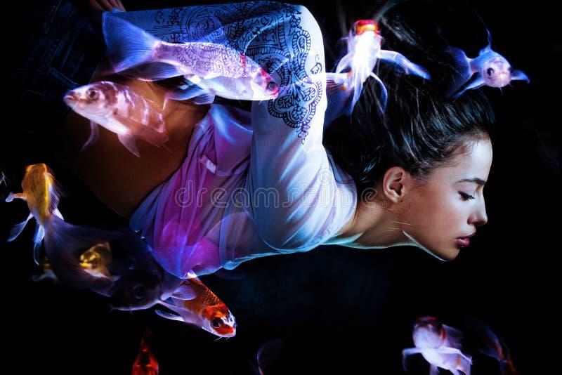 Mergulho da mulher da fantasia com peixes imagens de stock