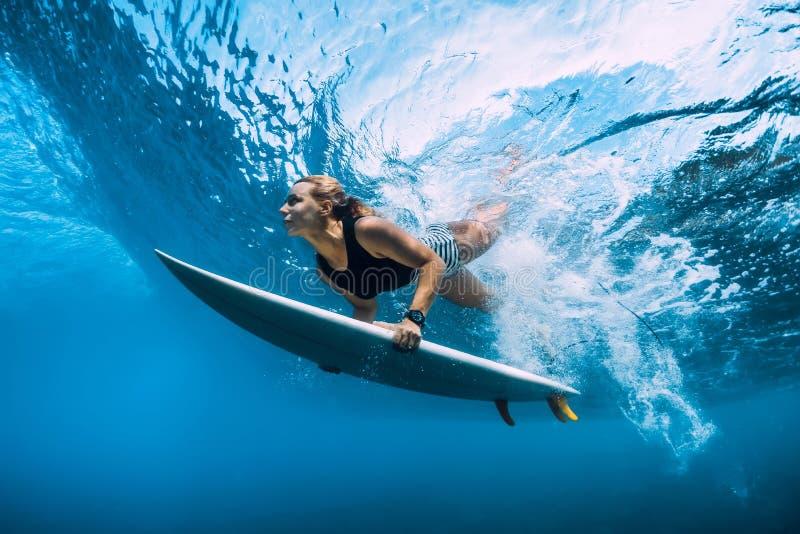 Mergulho da mulher do surfista debaixo d'água Mergulho de Surfgirl sob a onda imagem de stock royalty free
