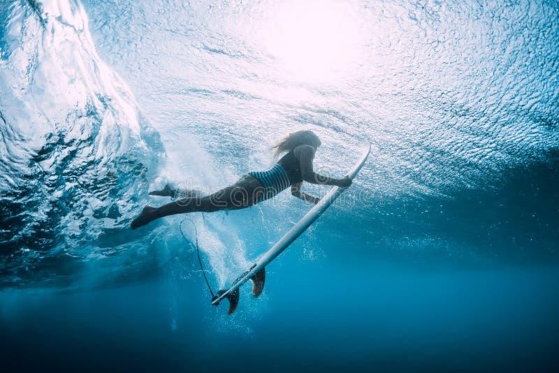 Mergulho da mulher do surfista subaquático com a onda azul inferior imagem de stock
