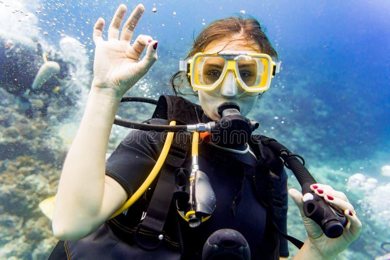 Mergulho da mulher no recife de corais que dá o sinal aprovado imagens de stock royalty free
