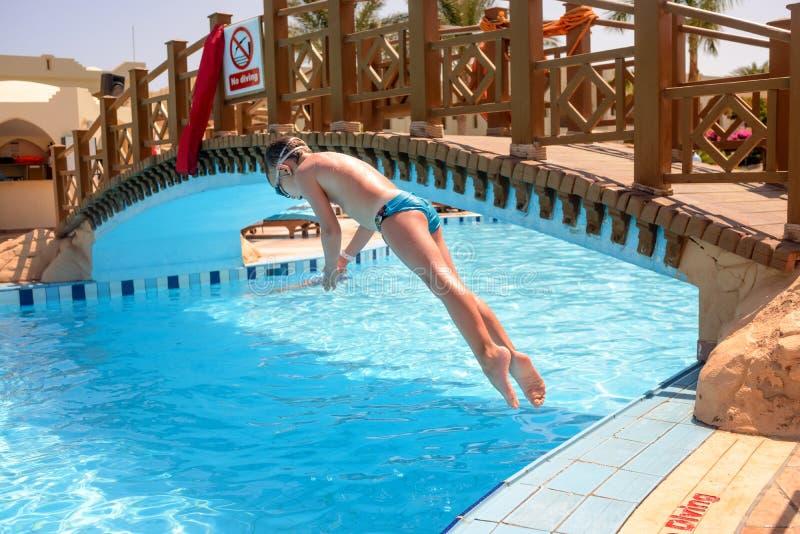 Mergulho do rapaz pequeno em uma piscina do recurso fotografia de stock royalty free