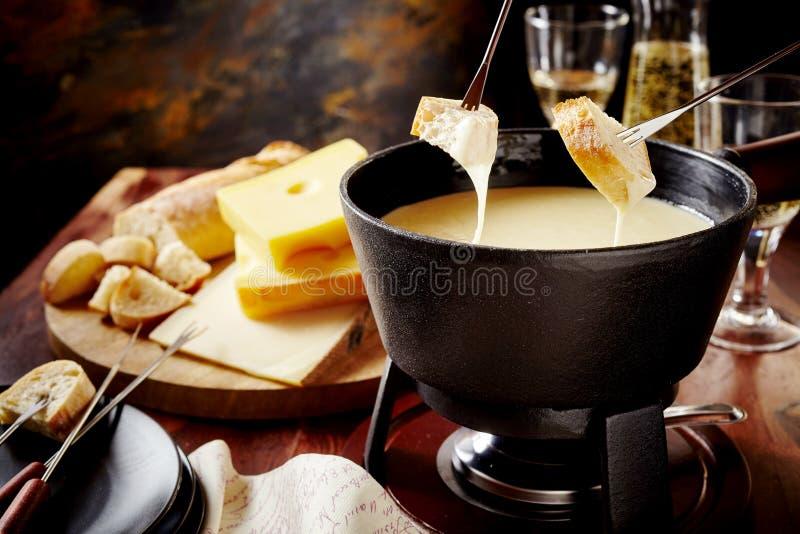Mergulho em um fondue de queijo delicioso imagem de stock royalty free