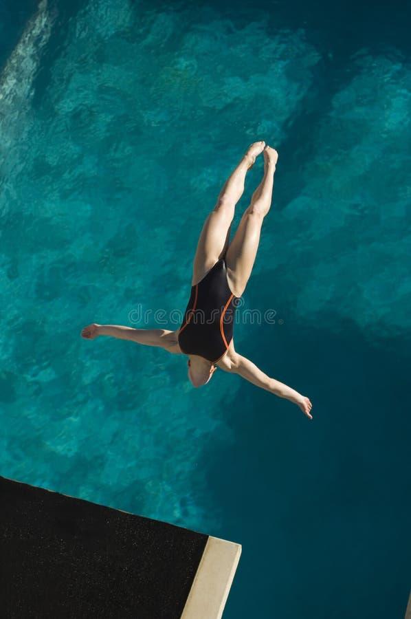 Mergulho fêmea do nadador no meio do ar fotografia de stock