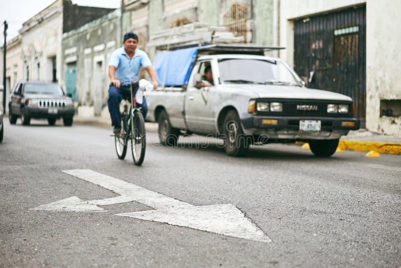 Merida/Iucatão, México - 1º de junho de 2015: O foco do sinal da seta na rua com o homem que monta a bicicleta e o carro obscuros fotos de stock royalty free