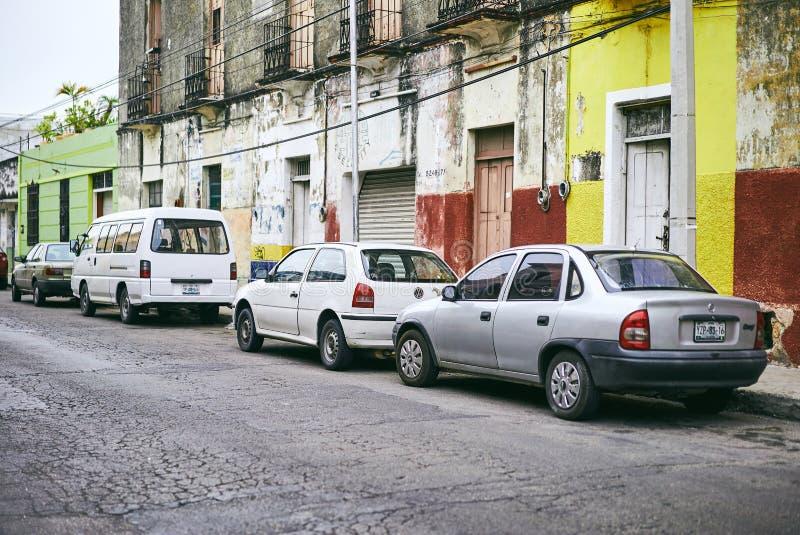 Merida/Iucatão, México - 1º de junho de 2015: Os carros que estacionam na frente do buiding velho contrariamente à parede amarela fotos de stock royalty free