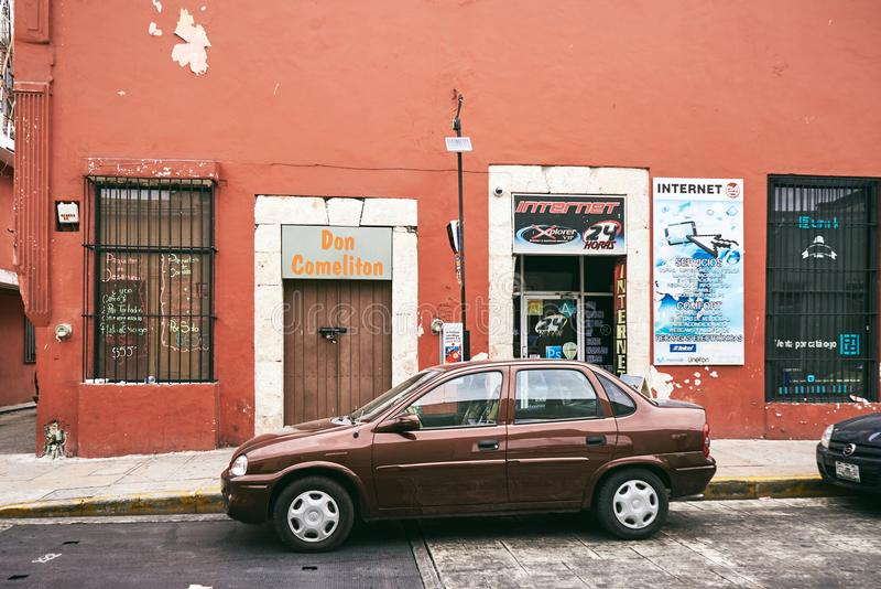 Merida/Iucatão, México - 31 de maio de 2015: O estacionamento marrom do carro na frente da casa com cor marrom pastel da parede imagens de stock