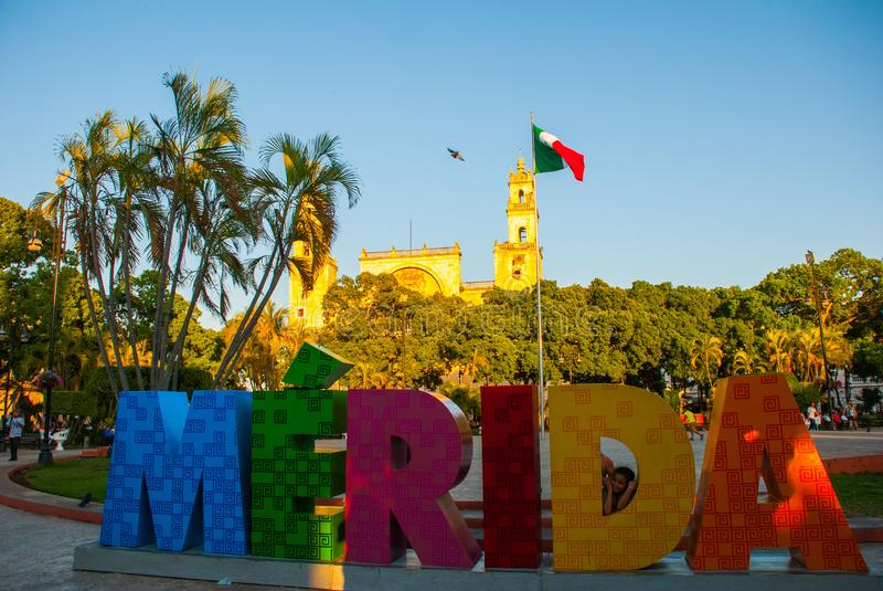 Merida, Mexico. Colorful Merida sign in Plaza Grande. San Ildefonso cathedral in the evening. Mexican flag flutters on air. Huge letters with the name of the stock photography