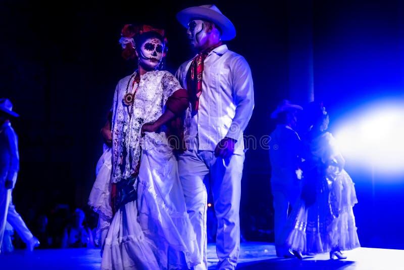 Dancing Catrina couples with skull make up for dias de los muertos with traditional dresses at Remate de Paseo Montejo. Merida, Mexico - October 27 2018: Dancing stock photos