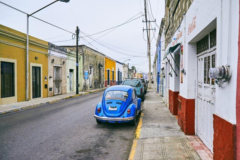 Merida/Yucatan, Mexico - Juni 1, 2015: Het uitstekende blauwe autoparkeren voor het oude rode en gele gebouw in Merdia, Yucata royalty-vrije stock foto's