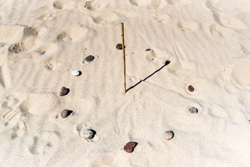 meridiana-sulla-spiaggia-fatta-di-un-bastone-e-delle-pietre-b-116892356.jpg