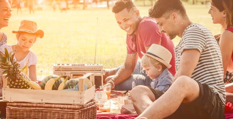 Merienda en el campo la familia feliz de la diversión con los niños y los amigos en el parque las familias raciales multi jovenes foto de archivo libre de regalías