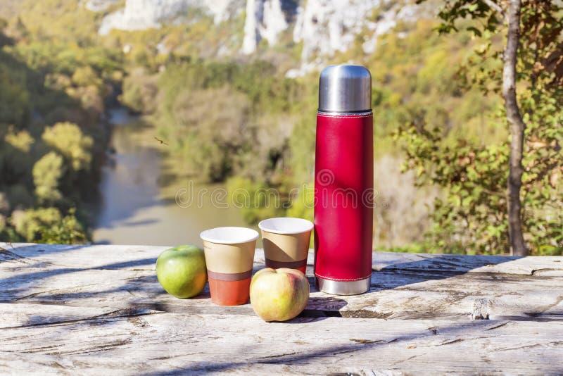 Meriende en el campo en la alta montaña con el termo, el café y manzanas rojos imagen de archivo libre de regalías