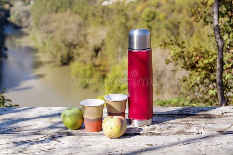 Meriende en el campo en la alta montaña con el termo, el café y manzanas rojos fotografía de archivo