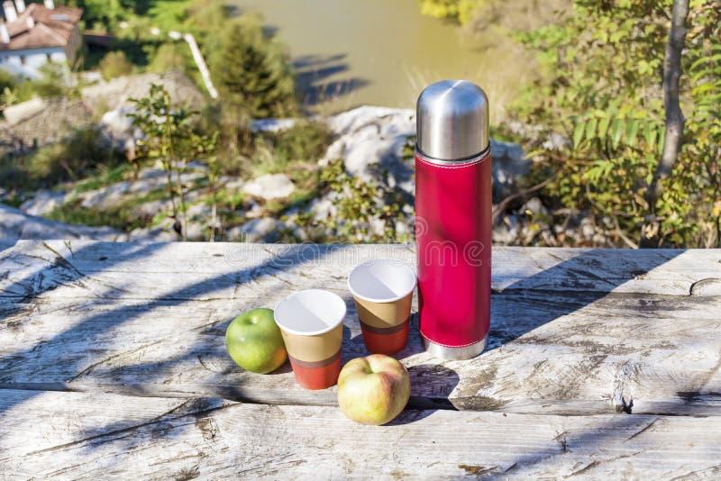 Meriende en el campo en la alta montaña con el termo, el café y manzanas rojos foto de archivo libre de regalías